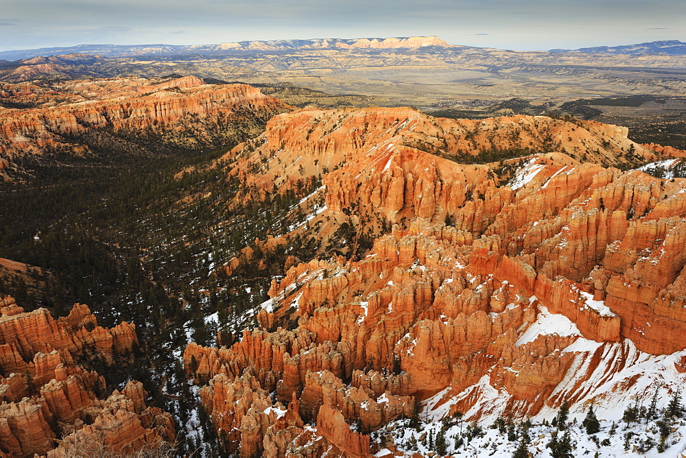 Hoodoos, trees and distant view with snow on a cloudy late winter afternoon, Bryce Point, Bryce Canyon National Park, Utah, United States of America, North America