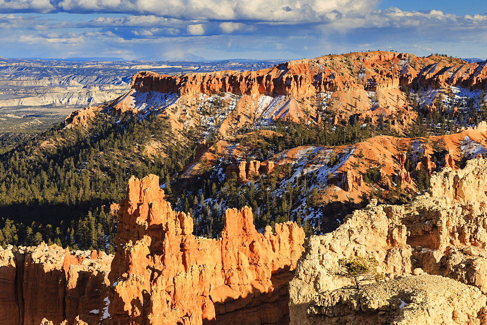 Late afternoon sun lights hoodoos and rocks through a cloudy sky in winter, Sunset Point, Bryce Canyon National Park, Utah, United States of America, North America