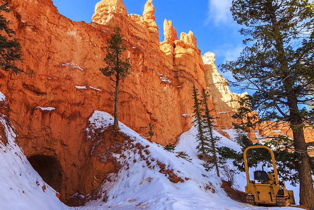 Snow clearing equipment at a tunnel through sunlit red rock in winter, Peekaboo Loop Trail, Bryce Canyon National Park, Utah, United States of America, North America