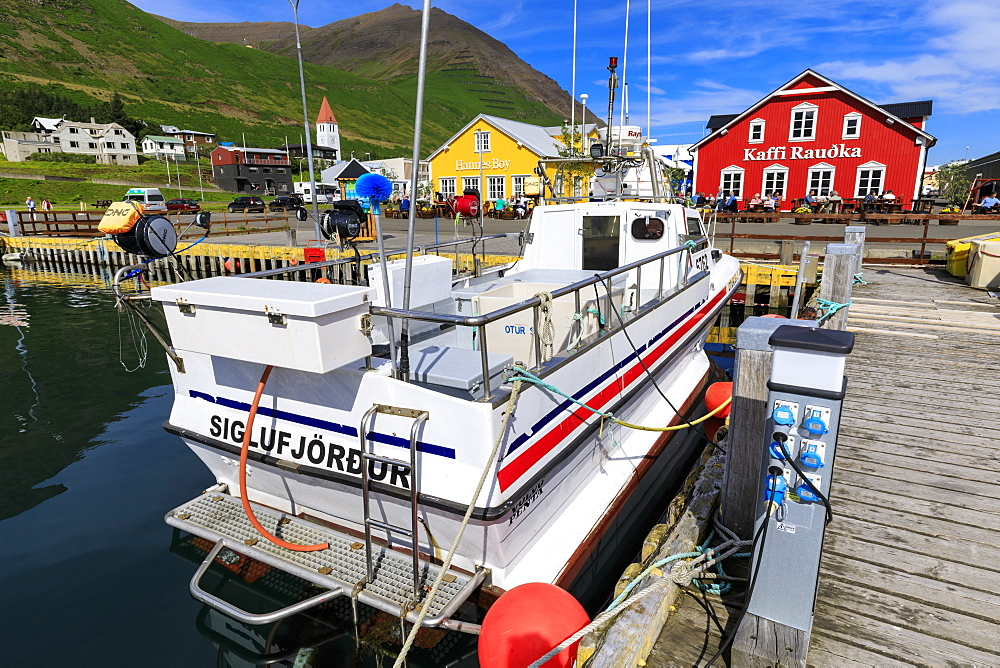 Church, busy cafes, fishing boat and mountains, Siglufjordur, (Siglufjorour), stunning Summer weather, North Iceland, Europe, Europe