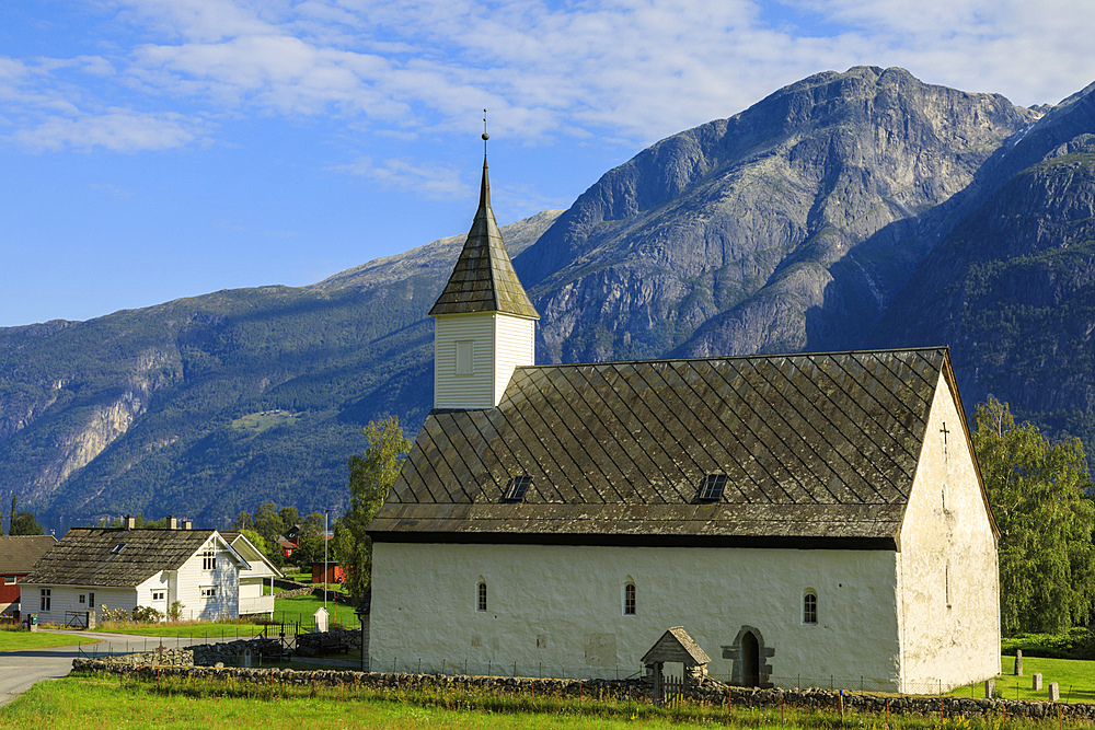 Old white church 1309, sunny day, mountain and village backdrop, Eidfjord, Norwegian Western Fjords, Norway, Europe