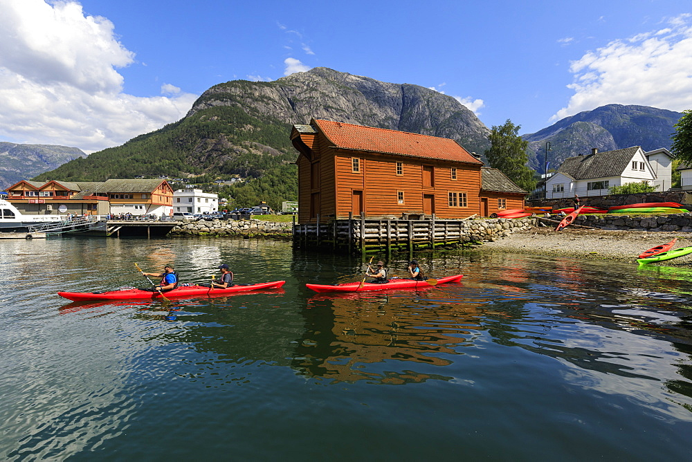 Sea kayakers head off, beautiful Eidfjord village, mountains and beach, sunny day, Norwegian Western Fjords, Norway