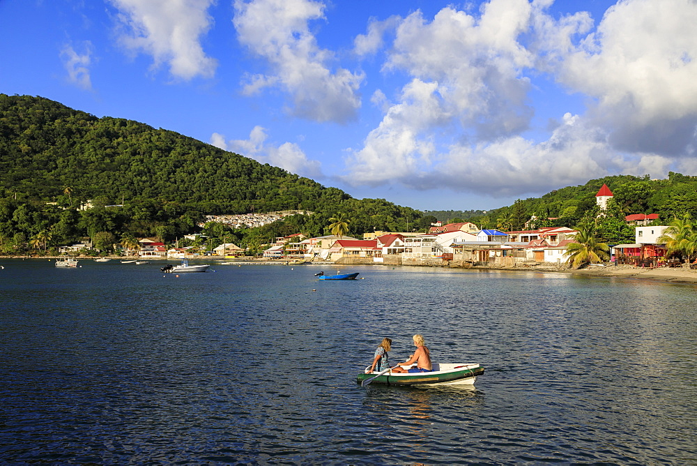 Deshaies waterfront, couple in rowing boat, Death In Paradise location, Saint Marie, Basse Terre, Guadeloupe, Leeward Islands, West Indies, Caribbean, Central America