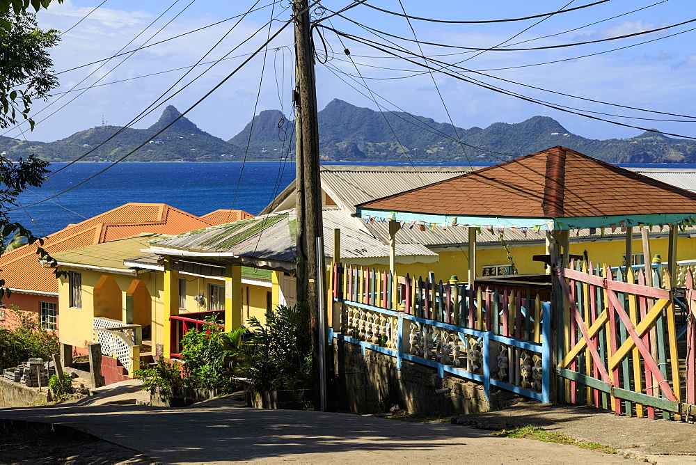 Quiet Caribbean, colourful buildings, main street, Mayreau, distant Union Island, Grenadines, St. Vincent and The Grenadines, Windward Islands, West Indies, Caribbean, Central America