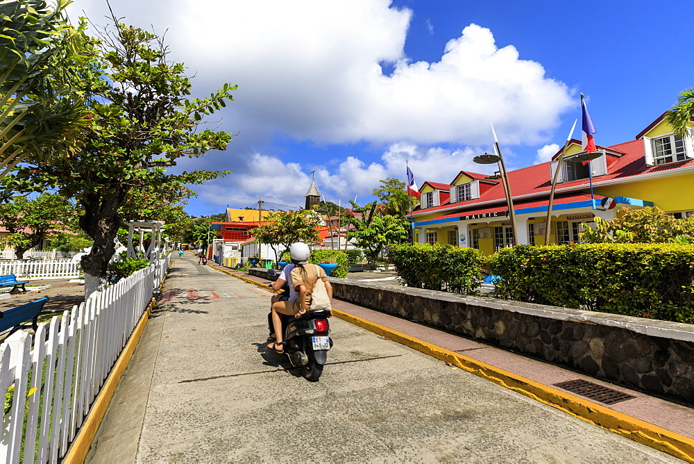Couple on moped, colourful Bourg des Saintes town, Terre de Haut, Iles Des Saintes, Les Saintes, Guadeloupe, Leeward Islands, West Indies, Caribbean, Central America