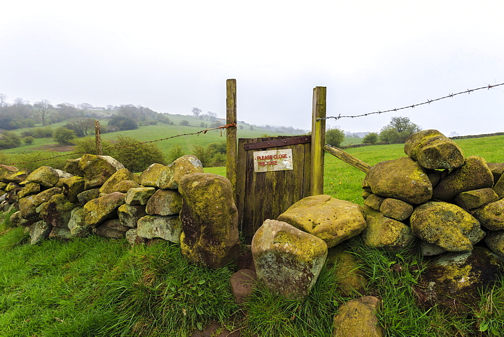Footpath gate and dry stone wall near Elton on a murky spring day, Peak District National Park, Derbyshire, England, United Kingdom, Europe