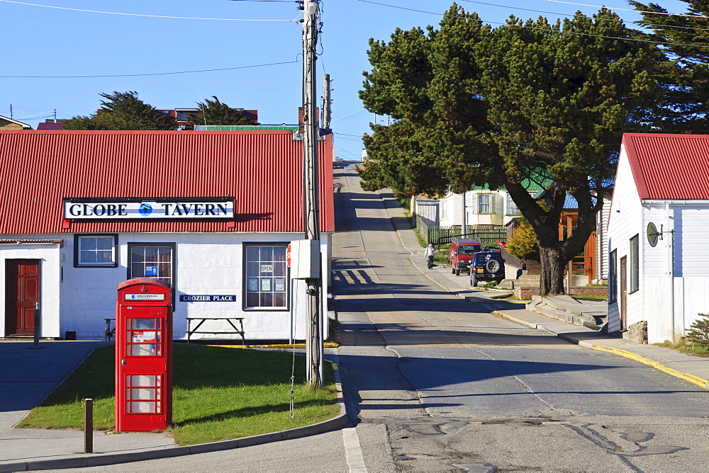 Red telephone box in Crozier Place with view up steep Philomel Street, Stanley, Port Stanley, East Falkland, Falkland Islands, South America