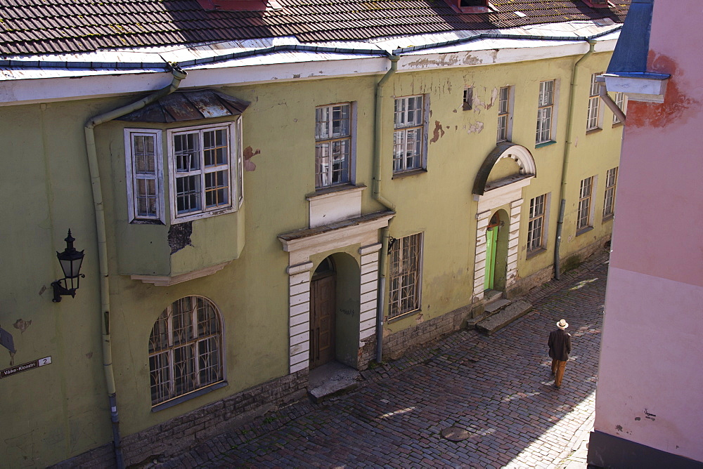 Man with hat in old street with pink and yellow coloured buildings, Tallinn, Estonia, Europe