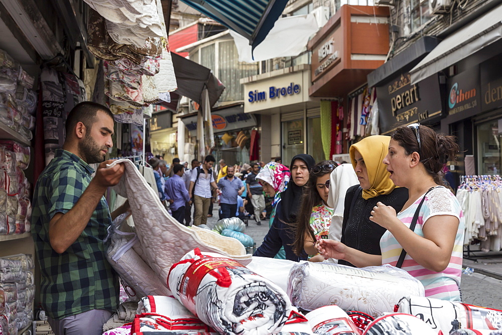 Turkish women making a bargain with a vendor (seller), street linking Grand and Spice Bazaars, Bazaar District, Istanbul, Turkey, Europe