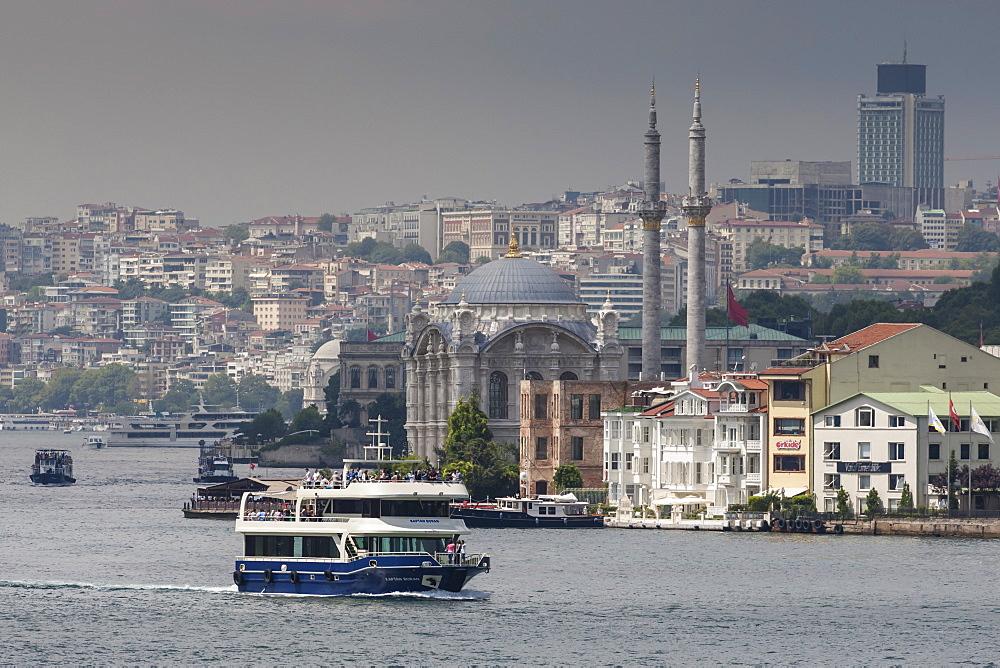 Ortakoy Mecidiye Mosque and passenger ferry, Ortakoy, from Bosphorus Strait with Istanbul city skyline behind, Istanbul, Turkey, Europe