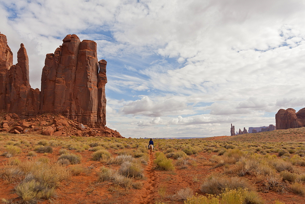 Navajo person rides a horse between rock formations, Monument Valley Navajo Tribal Park, Utah Arizona, United States of America