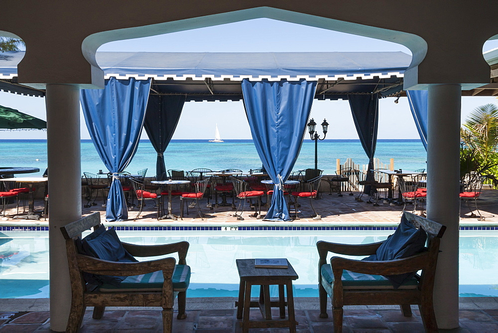 Hotel terrace with pool and view to a blue sea with passing catamaran, Cockburn Town, Grand Turk, Turks and Caicos, West Indies, Caribbean, Central America