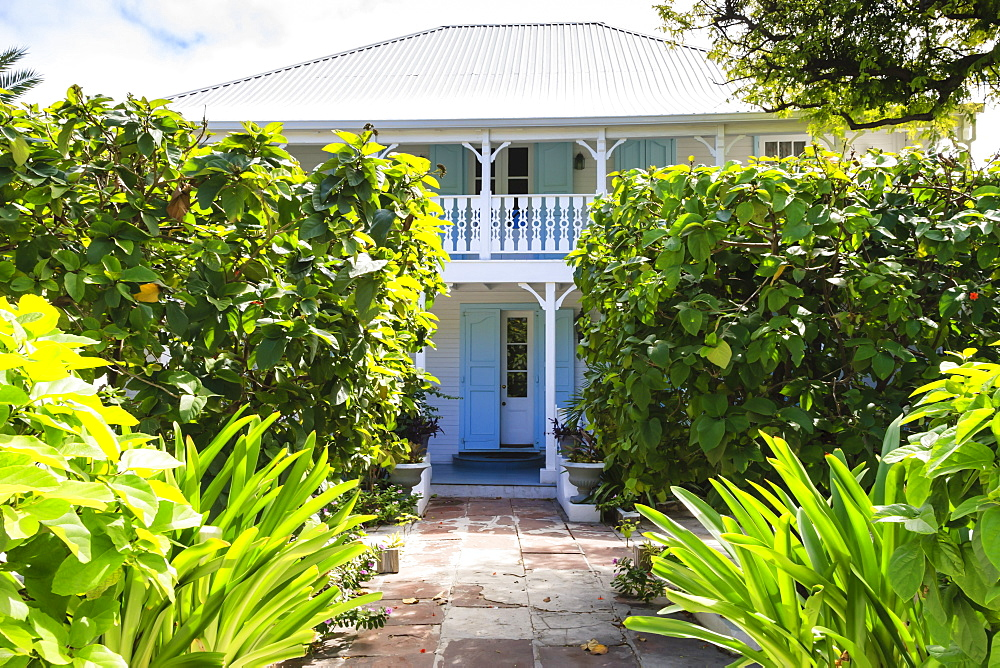 Old white wooden house with balcony, wriggly tin roof and lush garden, Cockburn Town, Grand Turk, Turks and Caicos, West Indies, Caribbean, Central America