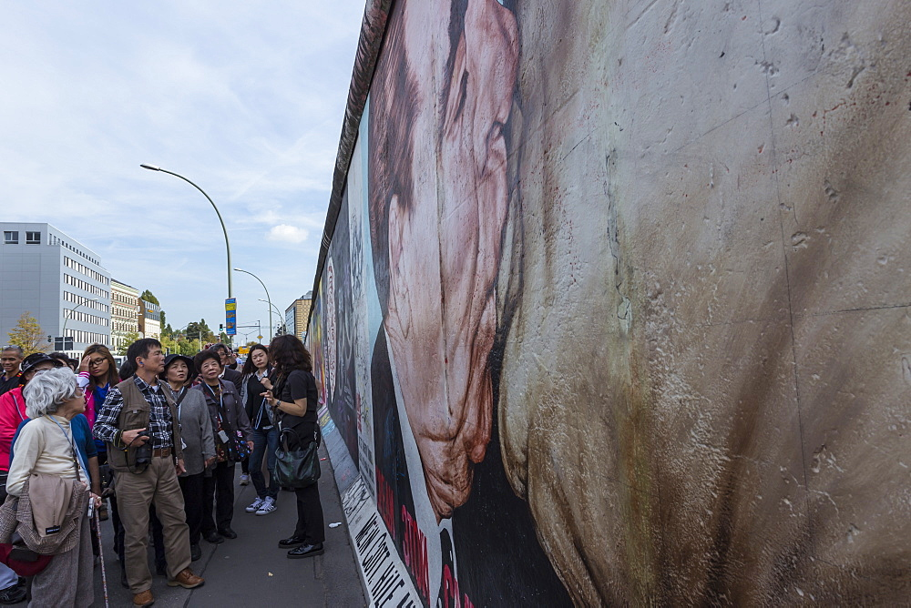 Tourists looking at mural My God, Help Me Survive Amid this Deadly Love by Dimitry Vrubel, Berlin Wall, East Side Gallery, Berlin, Germany, Europe