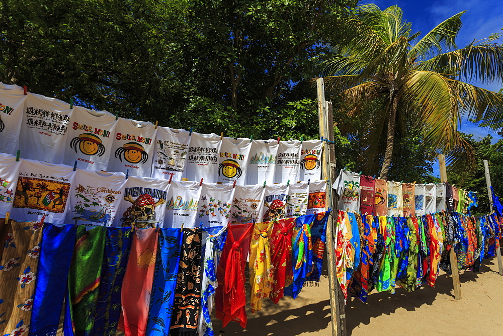 Colourful souvenir clothing on vendor stall with palm tree, beach, Saline Bay, Mayreau, Grenadines of St. Vincent, Windward Islands, West Indies, Caribbean, Central America