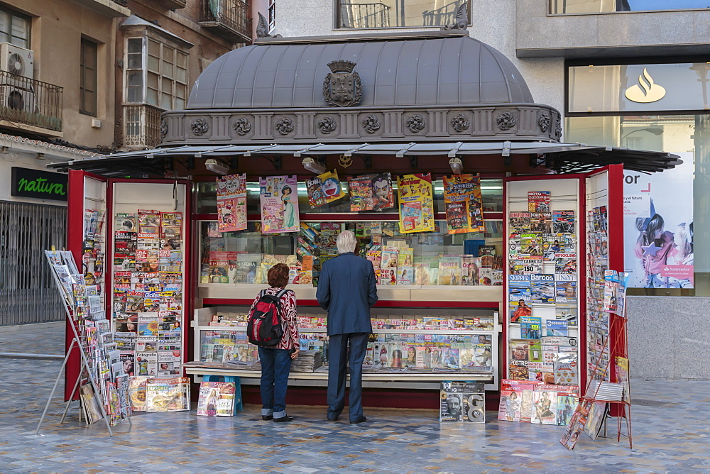 People stand at a red newspaper and magazine kiosk with fancy roof, Cartagena, Murcia Region, Spain, Europe