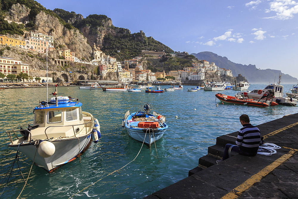 Fisherman working on harbour quayside with view towards Amalfi town and fishing boats, Costiera Amalfitana (Amalfi Coast), UNESCO World Heritage Site, Campania, Italy, Europe