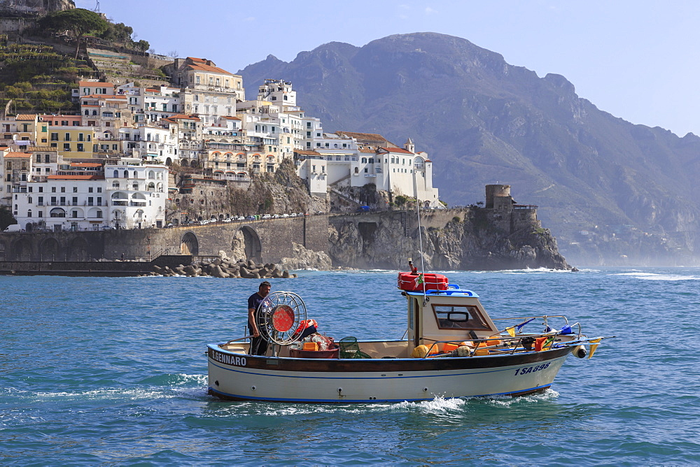 Fisherman in fishing boat heads out to sea from Amalfi harbour, with view towards Amalfi town, Costiera Amalfitana (Amalfi Coast), UNESCO World Heritage Site, Campania, Italy, Europe