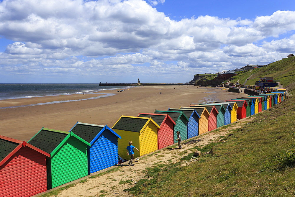 Children kick football near colourful beach huts above West Cliff Beach, Whitby, North Yorkshire, England, United Kingdom, Europe