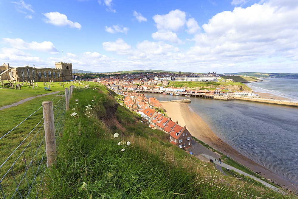 St. Mary's Church and churchyard with view across Tate Hill Beach and town houses to West Cliff, Whitby, North Yorkshire, England, United Kingdom, Europe