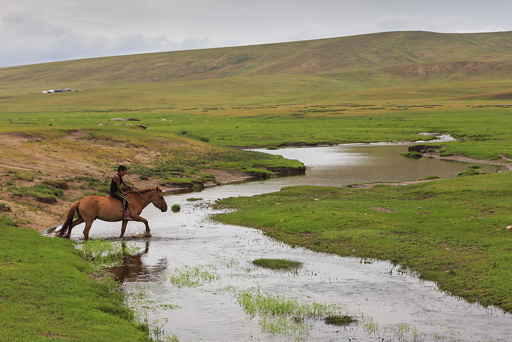 Nomadic boy rides his horse through river with gers int he distance at summer nomad camp, Khujirt, Uvurkhangai (Ovorkhangai), Central Mongolia, Central Asia, Asia