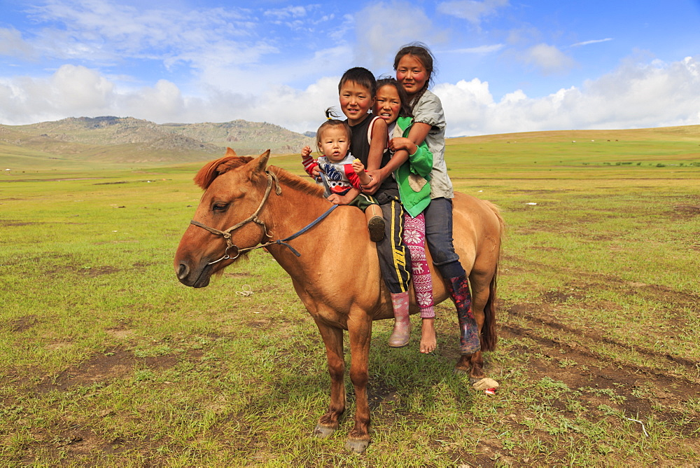 Four nomad siblings on their tame horse at summer nomad camp, Khujirt, Uvurkhangai, Central Mongolia, Central Asia, Asia
