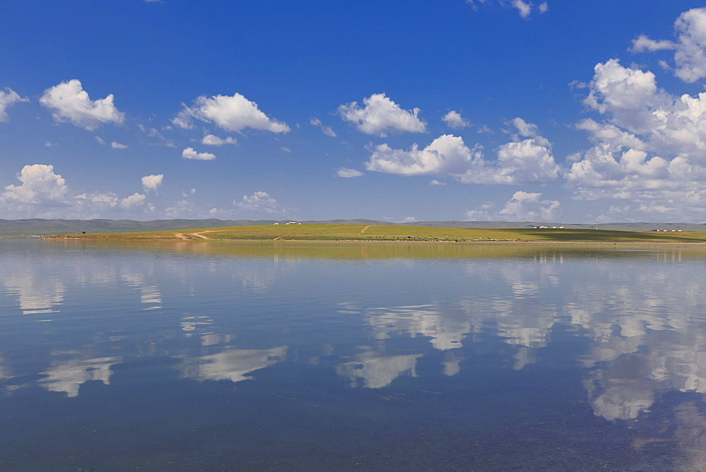 Fluffy clouds in a blue summer sky, reflected in a lake, distant reflected gers, Arkhangai, Central Mongolia,Central Asia, Asia
