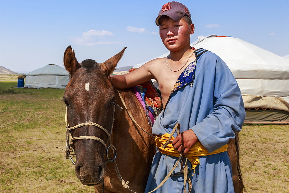Portrait of nomad in deel with his horse, Nomad gers, Khogno Khan Uul Nature Reserve, Gurvanbulag, Bulgan, Northern Mongolia, Central Asia, Asia