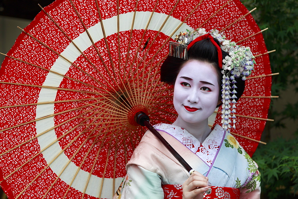 Portrait of smiling geisha in floral robes with red umbrella in summer, Kyoto, Japan, Asia