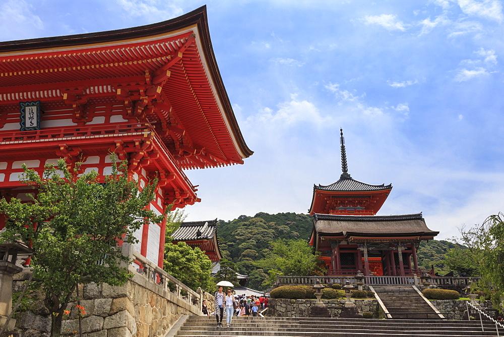 Visitors with sun umbrella in summer, vermillion temple entrance buildings, Kiyomizu-dera, Southern Higashiyama, Kyoto, Japan, Asia