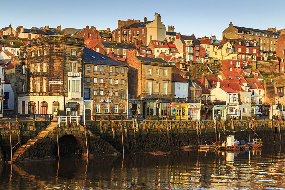 Townhouses, bars and restaurants on Pier Road, West Side of River Esk, lit by low sun in winter, Whitby, North Yorkshire, England, United Kingdom, Europe