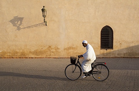 Muslim man dressed in white on bicycle in old quarter, Medina, Marrakech, Morocco, North Africa, Africa