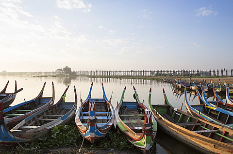 U Bein Bridge and traditional colourfully painted rowing boats on Taungthaman Lake at sunrise, Myanmar (Burma), Asia
