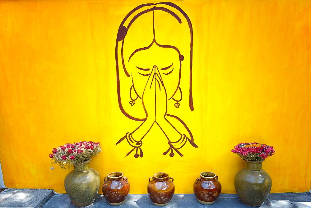Drawing of praying woman on a yellow wall in Lijiang, Yunnan, China, Asia