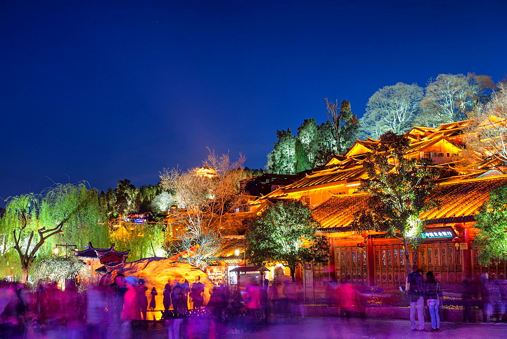 Colourfully illuminated traditional architecture and trees in the old town of Lijiang, UNESCO World Heritage Site, Yunnan province, China, Asia