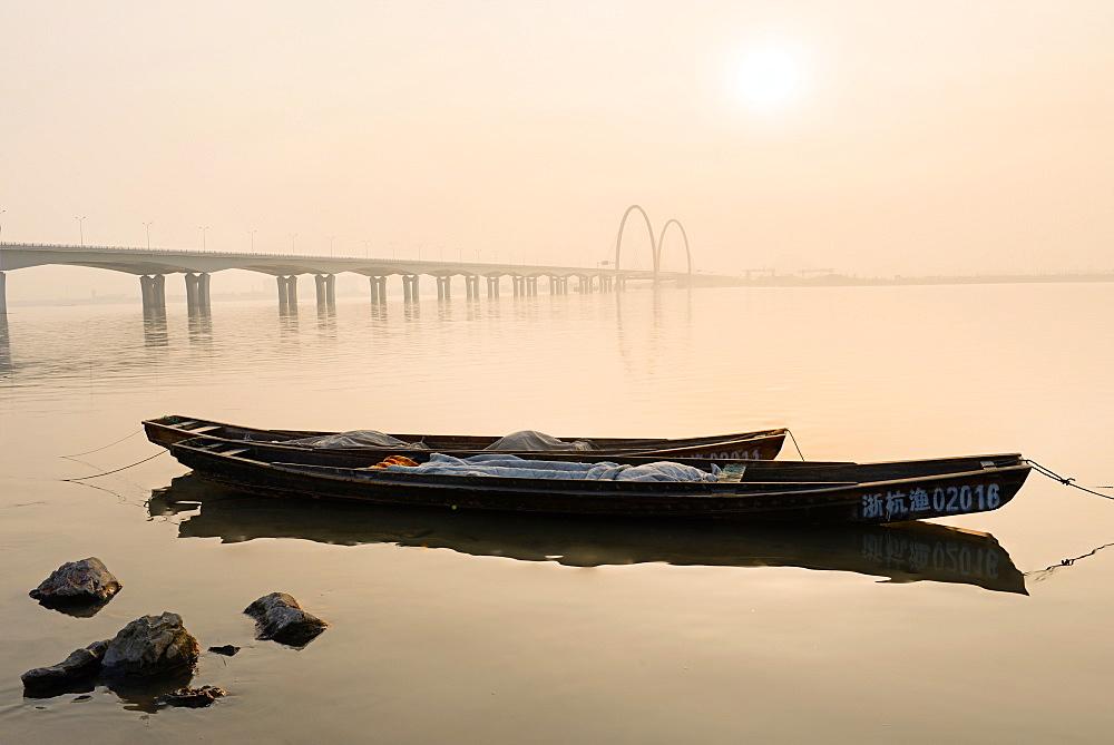 Fishing boats and modern bridge in mist at Qiantangjiang River in Hangzhou, Zhejiang, China, Asia