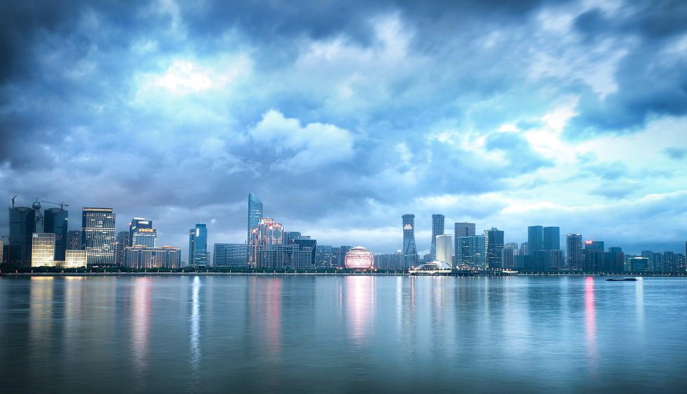 Blue hour shot of Jianggang district lights slowly coming to life under a dramatic sky, Hangzhou, Zhejiang, China, Asia