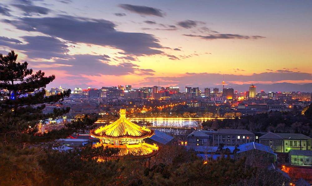 Illuminated pagoda and view towards the western part of Beijing city at nightfall, Beijing, China, Asia