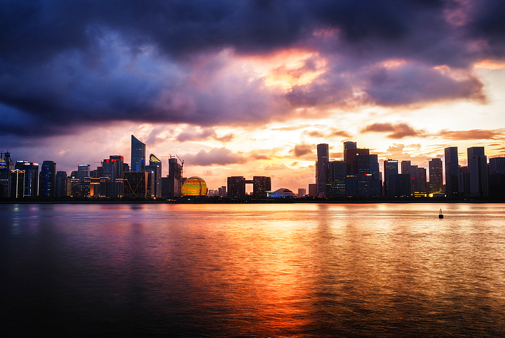 Dramatic clouds over Qianjiang River with skyline of Hangzhou´s new business district.