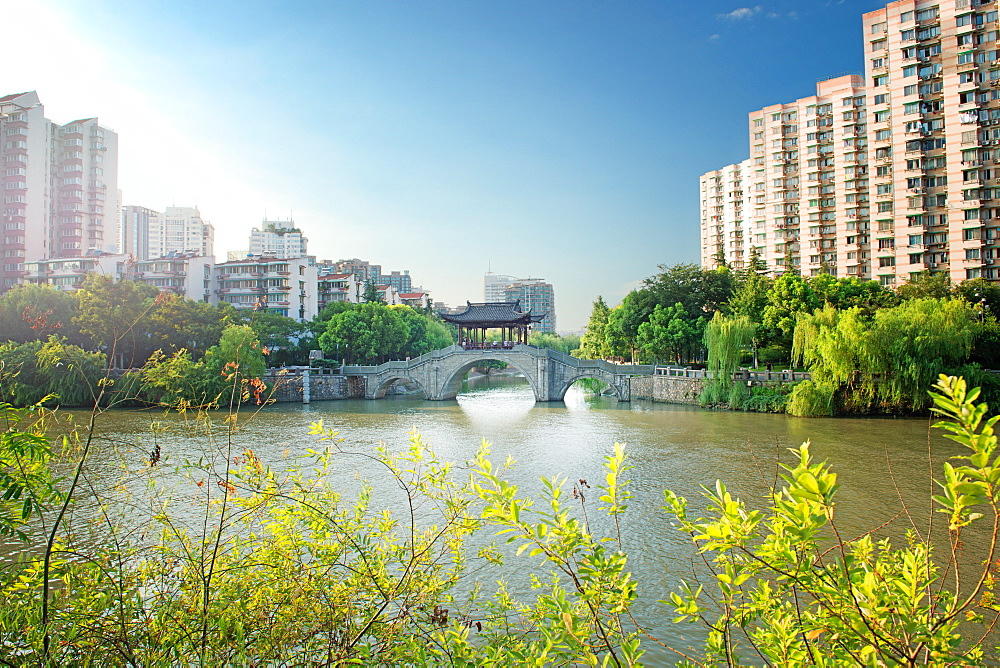 Stone bridge with pagoda style roofing, flanked by old style apartment buildings on the left and newer ones on the right, Hangzhou, China, Asia - 1171-275