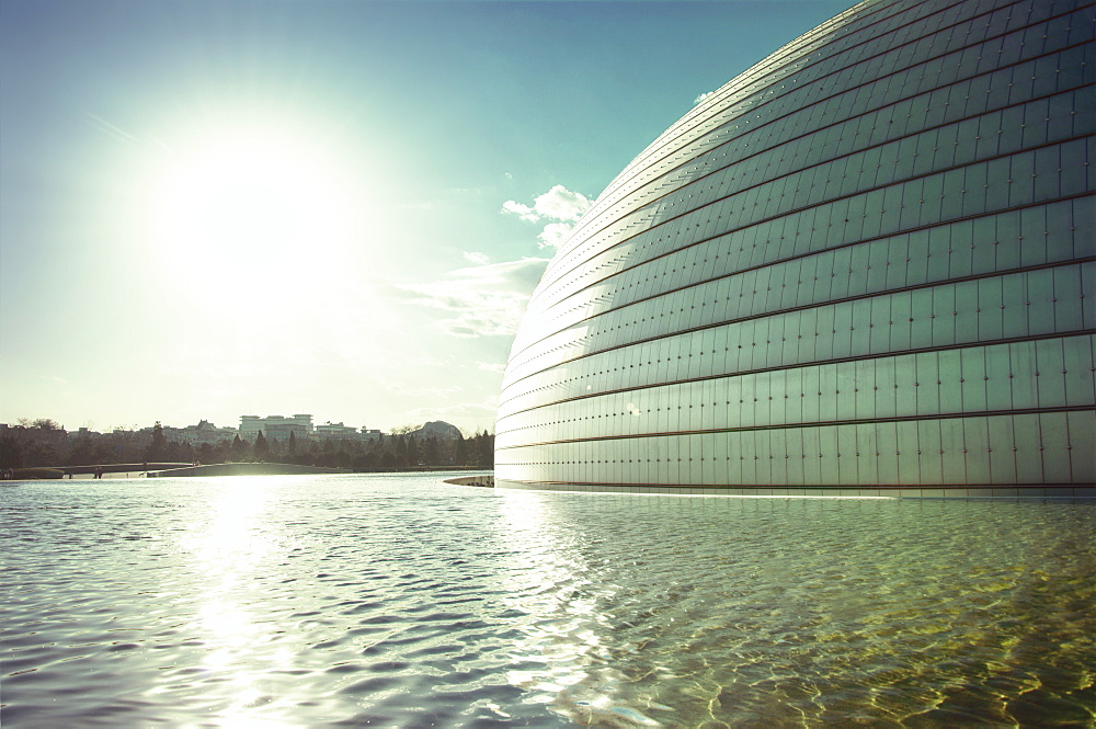Sun and a partial view of Beijing Opera building with pool, Beijing, China, Asia