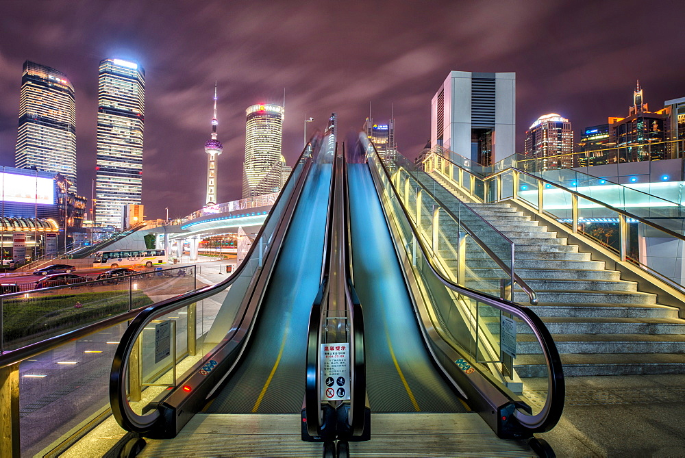 A modern, open-air escalator with Pudong cityscape at night, Shanghai, China, Asia