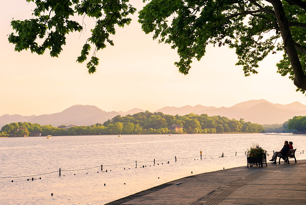 West Lake shore with hilly landscape and silhouettes, Hangzhou, Zhejiang, China, Asia