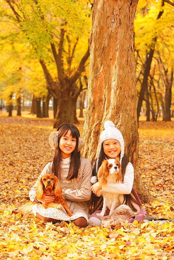 Girls Holding Their Dog In Leaves