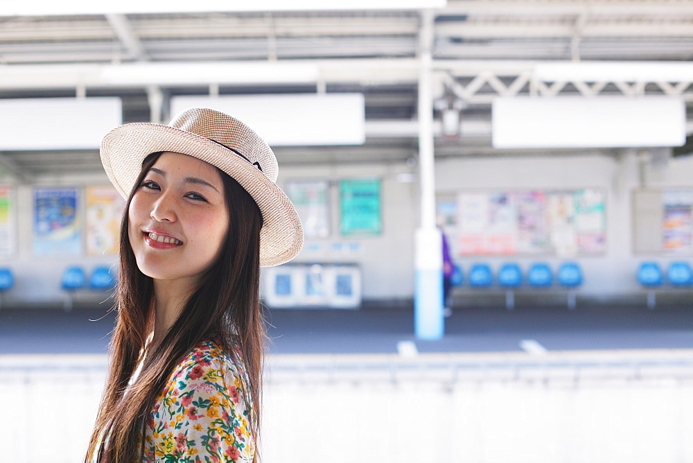 Portrait of a smiling Japanese woman with a hat at the station