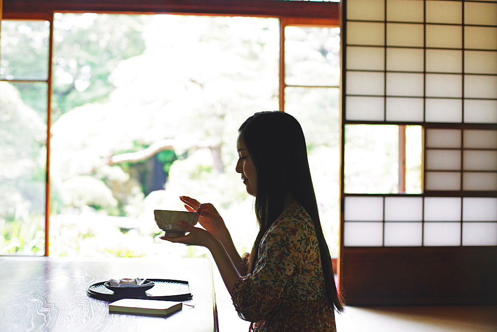 Japanese woman drinking green tea in a traditional Japanese house