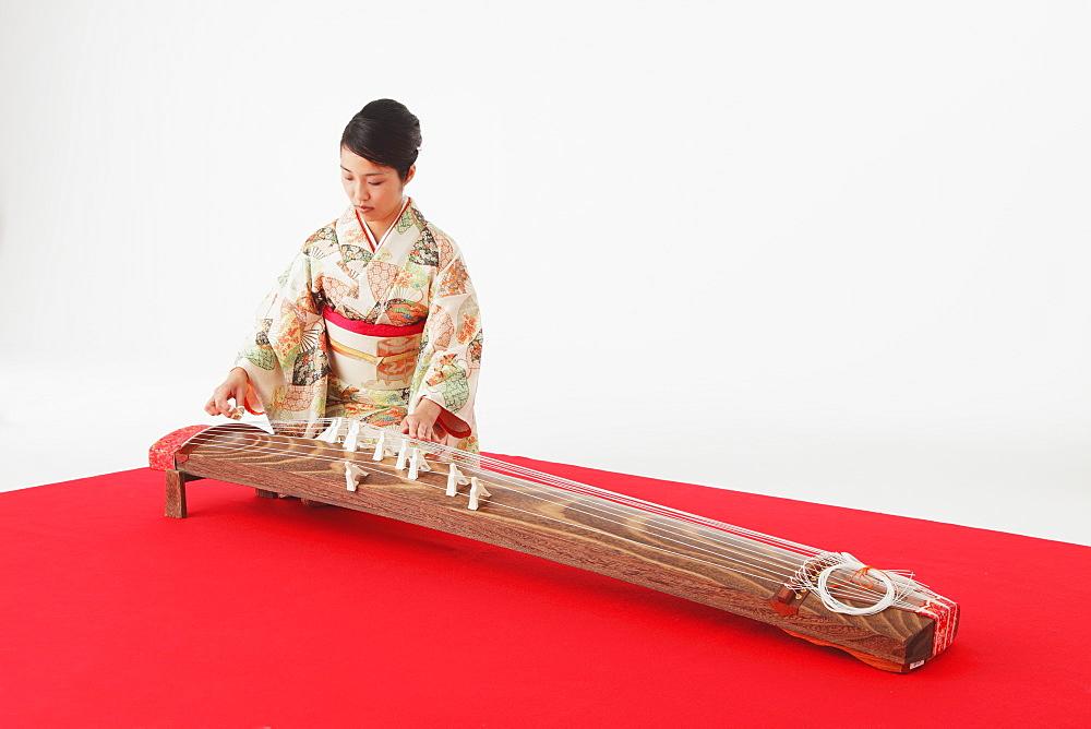 Japanese woman in a kimono playing the koto