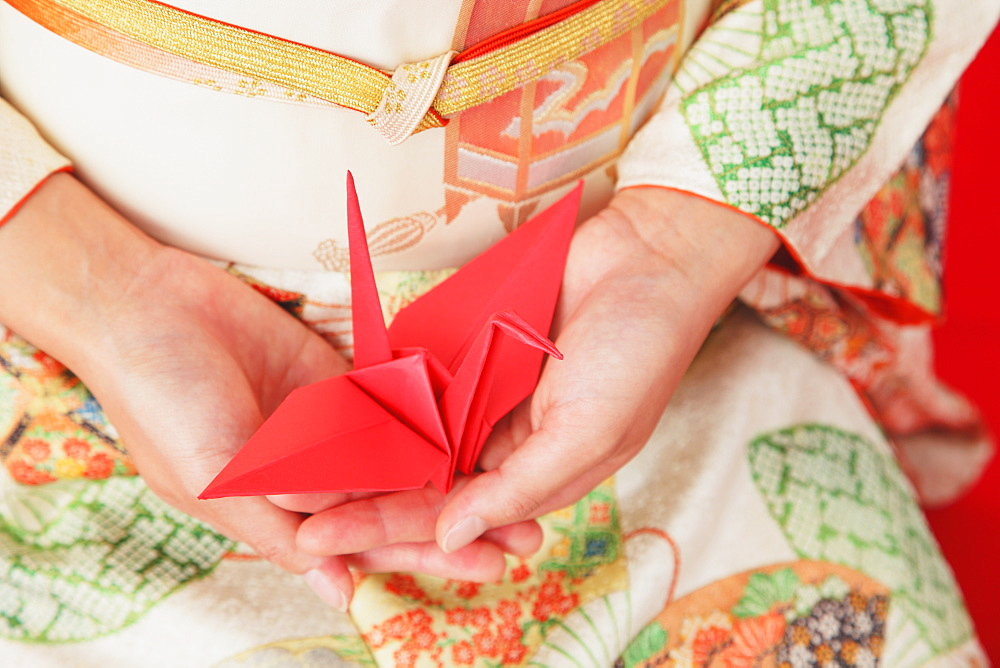 Close up of a Japanese woman in a kimono holding an origami of a crane