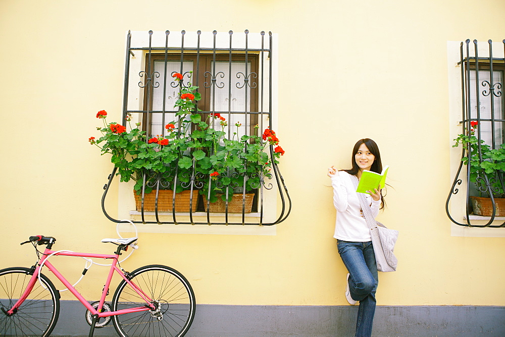 Young Woman  Leaning against Wall and Reading Book
