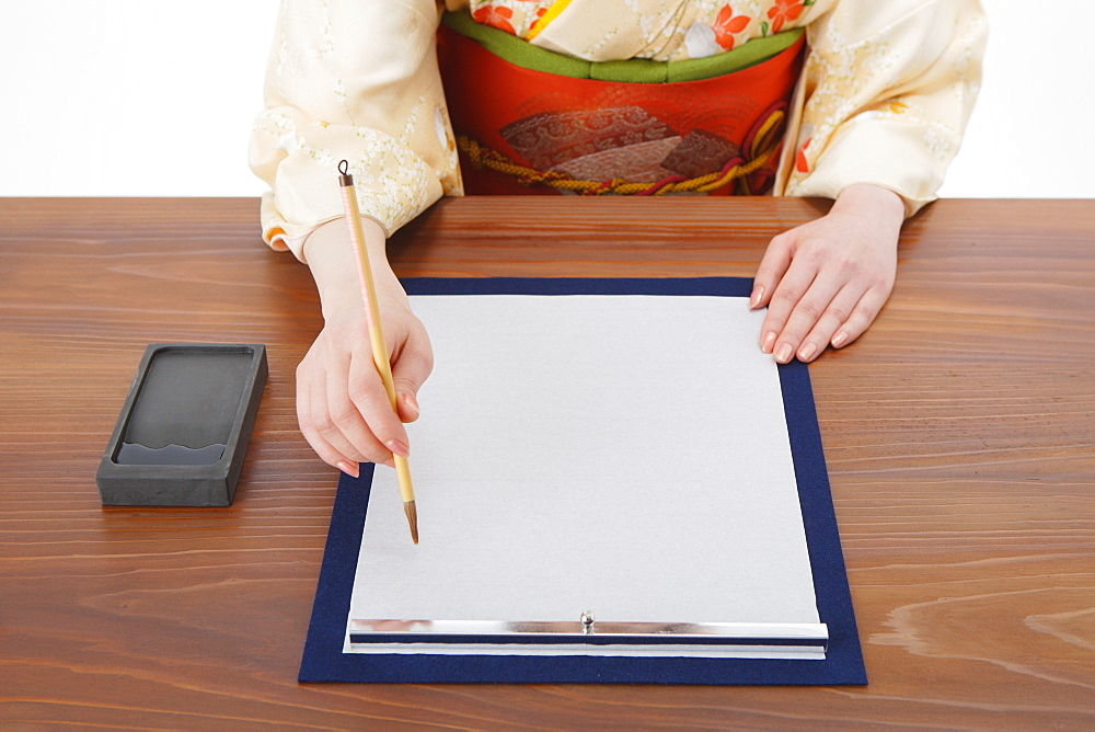 Woman Writing Calligraphy on Paper